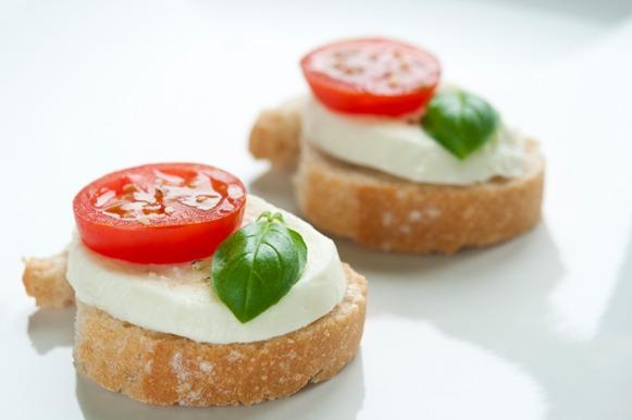 canapé de queijo branco, tomatinho e uma folha verde