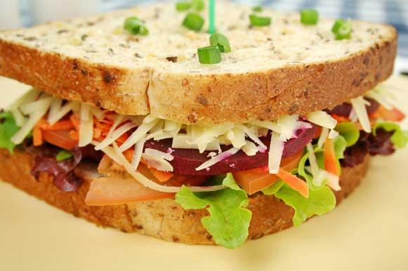 Sanduíche com folhas verdes, tomates, beterraba, queijo e alho-poró